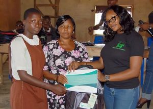 The IAF Operations Executive and a teacher of the Aglican Grammar School presenting a scholarship award of outstanding performance to a student